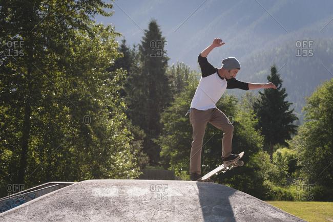 Skateboarder performing stunt on ramp in skate park