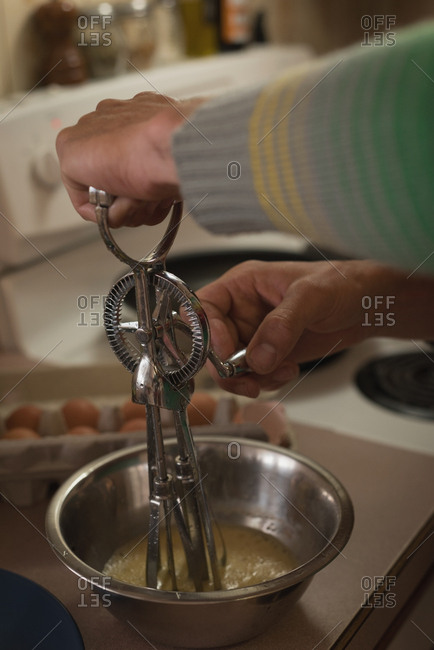 Close-up of mans hand whisking egg in kitchen