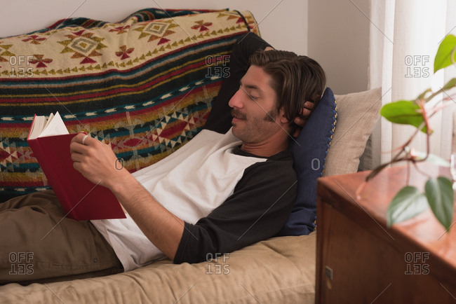Man reading a novel in living room at home