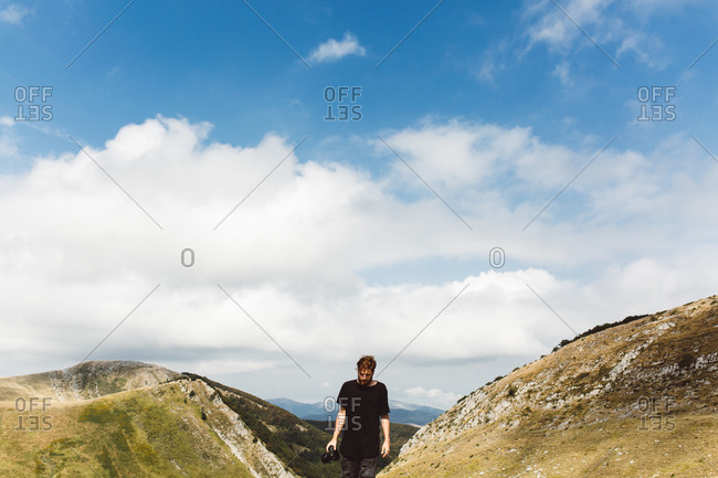 Tourist man hiking and trekking in picturesque mountains.