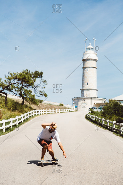 Young skateboarder man taking a ride on asphalt road at lighthouse.