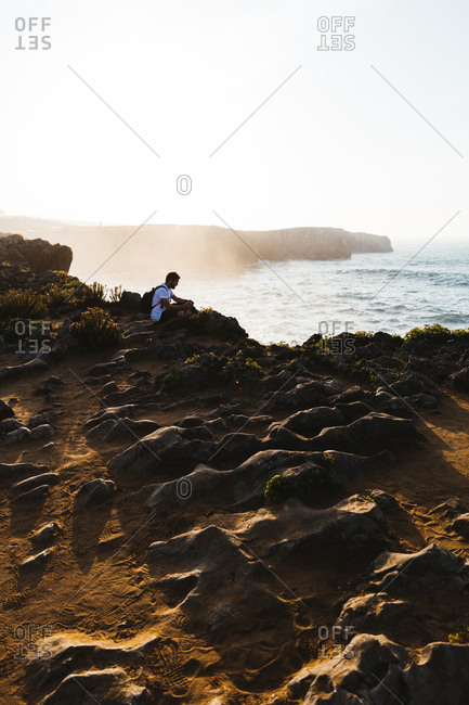 Man sitting on cliff - Offset