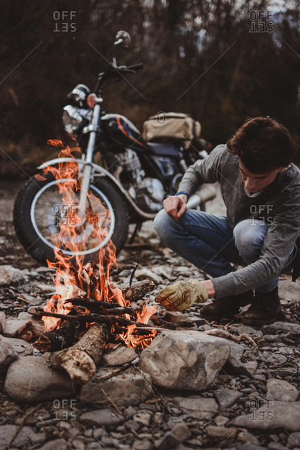 Man keeping campfire burning adding woods on background of parked motorcycle on rocky shore.