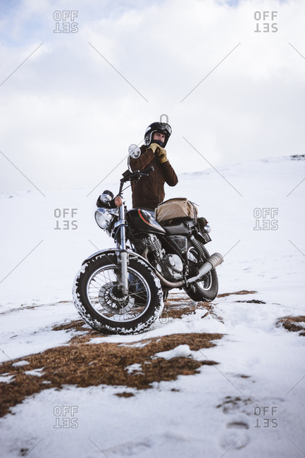 Man with motorcycle in snowy highlands