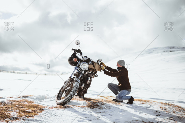 Side view of man arranging motorcycle while traveling alone across snowy mountains valley.