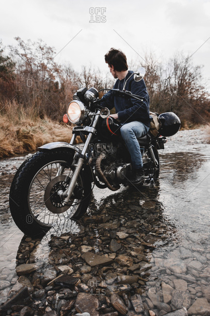 Anonymous man on motorcycle riding through water of creek in autumnal mountains while traveling alone.