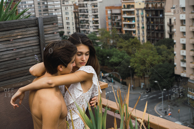 Couple touching each other lovingly on balcony