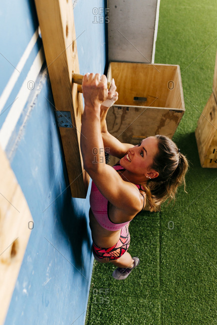 Determined woman climbing wall