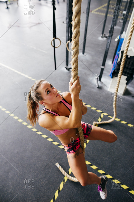 Young determined woman in sportswear determined on climbing rope in modern gym.