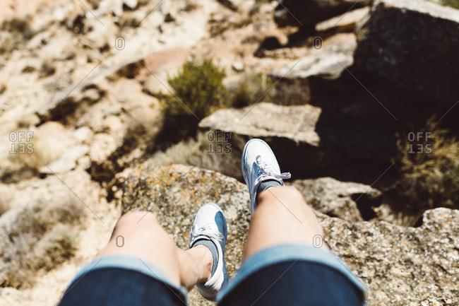 Legs of unrecognizable man hanging over cliff in desert.