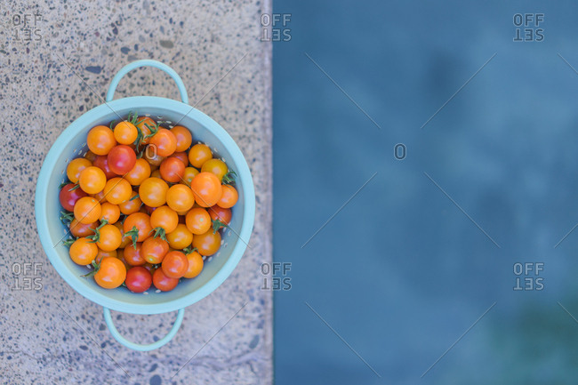 Close-up shot of ripe cultivated cherry tomatoes in blue bowl on stone table.