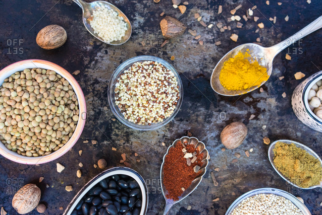 Spoons and bowls with assortment of seasonings and spices on weathered surface.