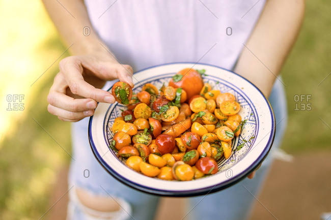 Faceless shot of woman holding plate with cherry tomatoes in spices and oil.