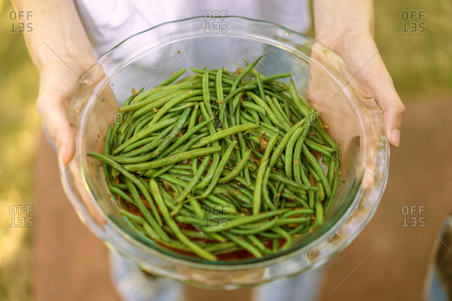 Woman holding bowl with green beans