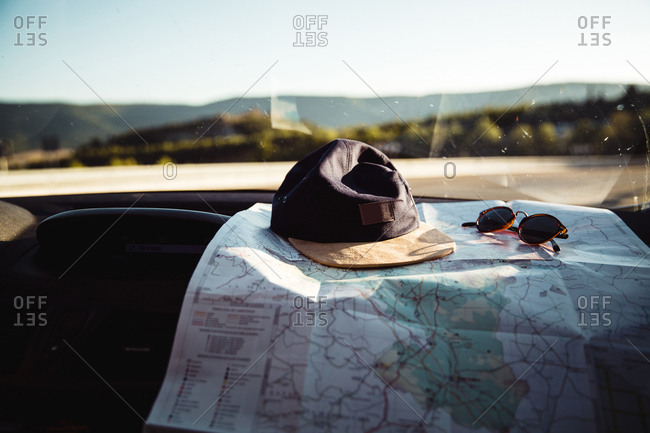 Cap, sunglasses and map lying on dashboard in passenger compartment of car.