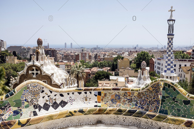 Barcelona, Spain - May 27, 2015: The Park Guell is an Antoni Gaudi-designed public park system composed of gardens and architectonic elements located on Monte Carmelo in Barcelona. Here the curved serpentine bench made out of ceramics