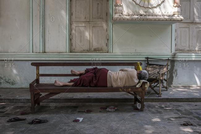 Monywa, Myanmar - 24 September 2016: Man sleeping on a bench at Thanboddhay Paya complex