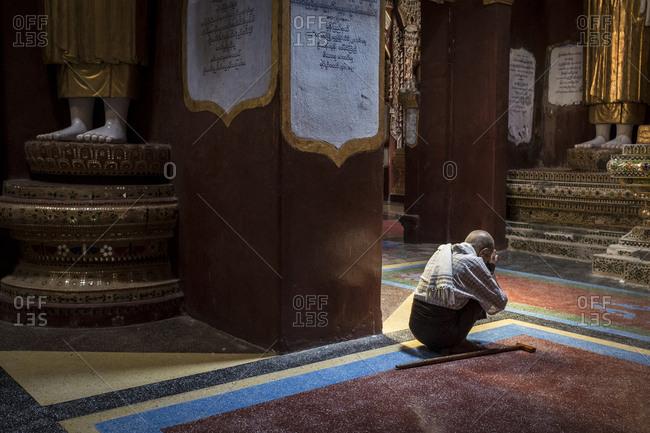 Monywa, Myanmar - 24 September 2016: Man praying to a statue of Buddha inside Thanboddhay Paya main temple
