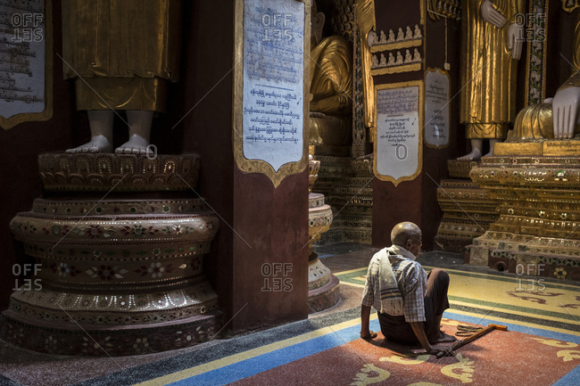 Monywa, Myanmar - 24 September 2016: Man sitting in front of a statue of Buddha inside Thanboddhay Paya main temple