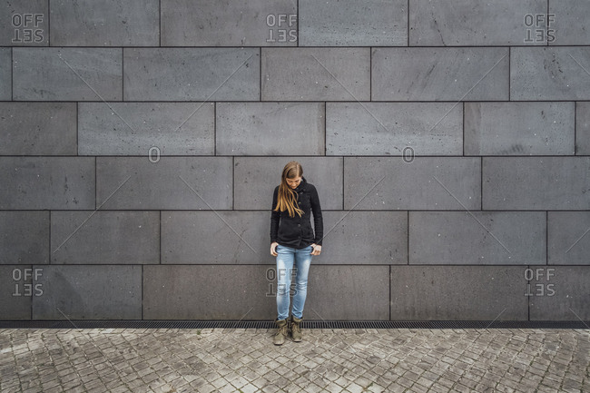Young woman standing in front of grey facade looking up