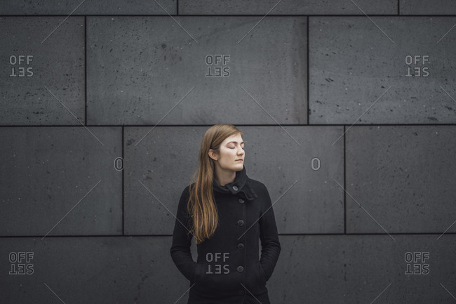 Young woman with eyes closed standing in front of grey facade