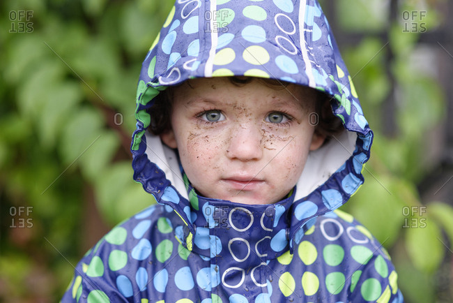 Portrait of little boy with dirty face wearing hooded jacket in rain