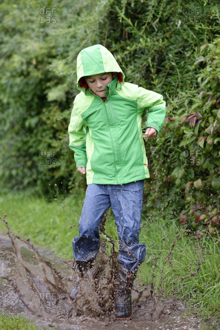 Boy wearing hooded anorak jumping into a muddy puddle