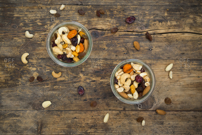 Two glasses of trail mix on dark wood