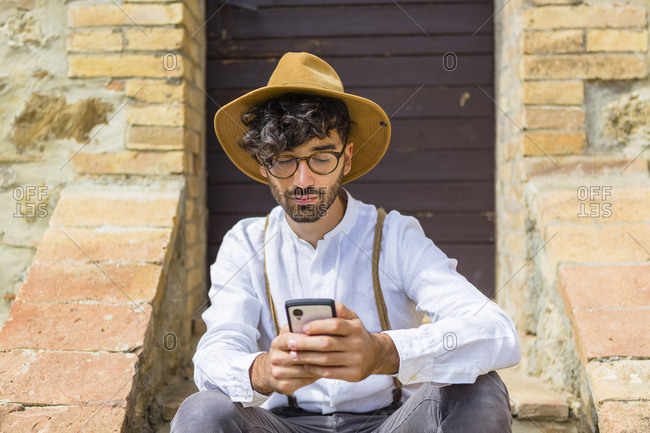 Man wearing old-fashioned clothes using cell phone