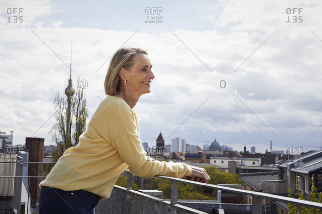 Smiling mature woman on balcony looking at view