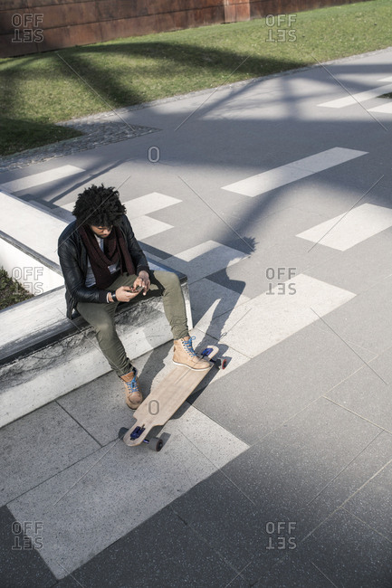 Man sitting in skate park with long board typing on smartphone