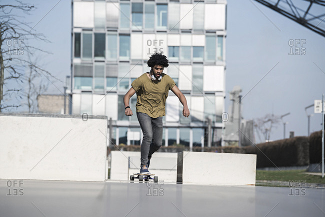 Young man riding long board in skate park