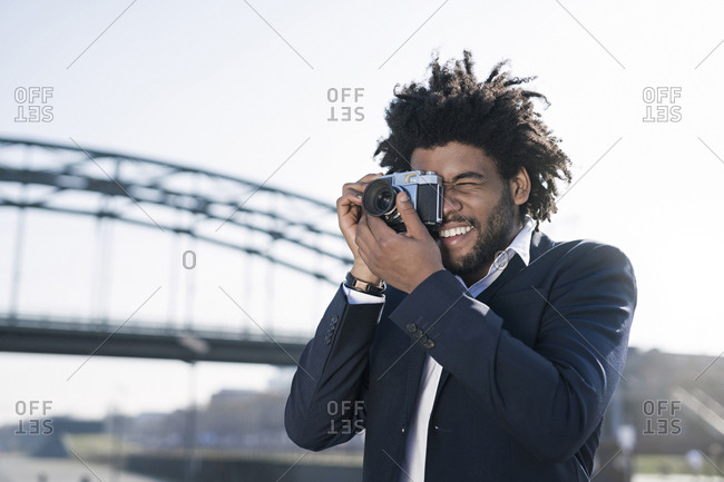 Smiling man in suit at the riverside taking a picture with a vintage camera