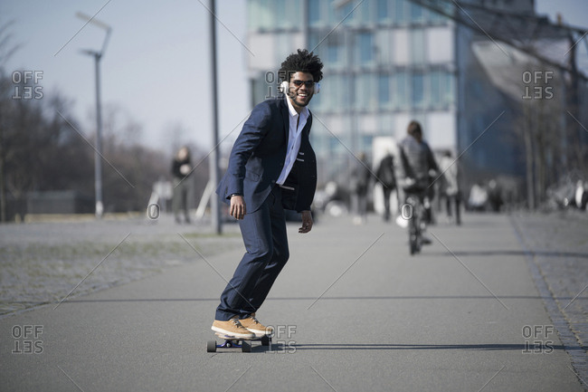 Smiling businessman riding long board in front of skyscraper