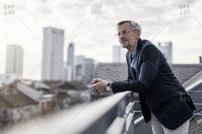 Grey-haired businessman standing on balcony looking over city
