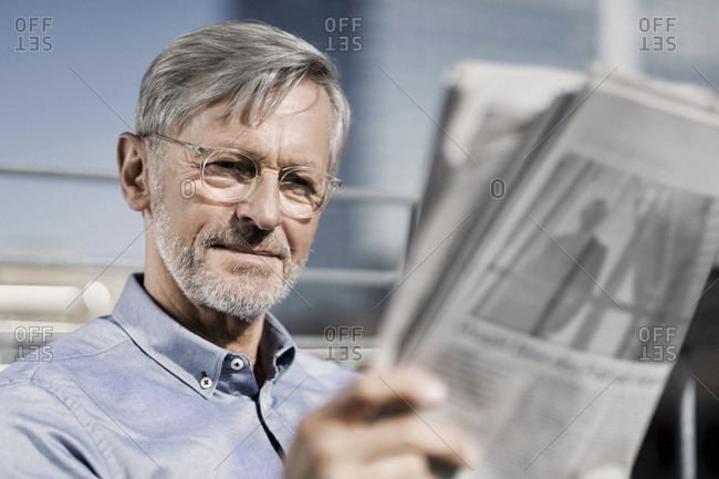 Grey-haired man reading newspaper