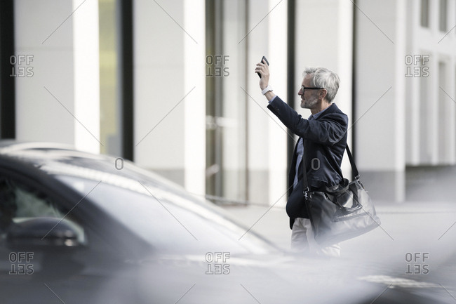 Grey-haired businessman calling a taxi in the city