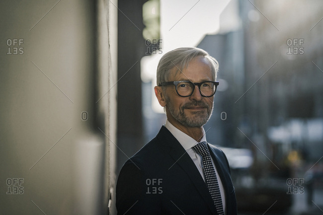 Portrait of grey-haired businessman in the city