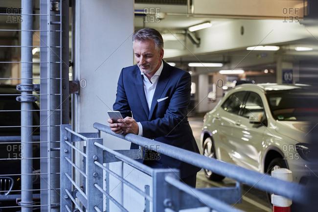 Businessman using smartphone in parking garage