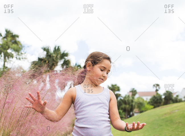 Little girl plays with tropical weeds