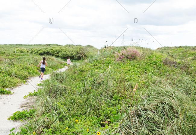 Sisters run along a beach path