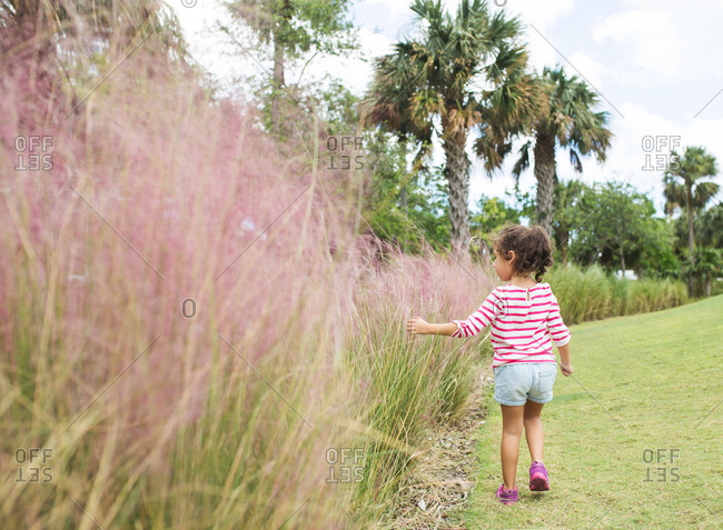Little girl walks along tropical path