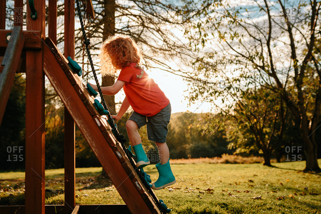 Child climbing wall with leaf in hair