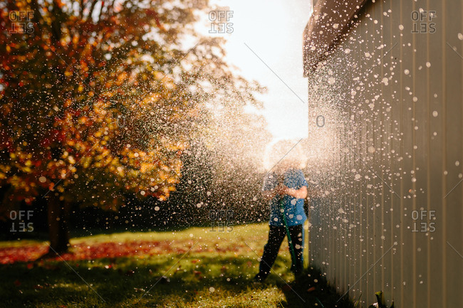 Child spraying hose from around corner
