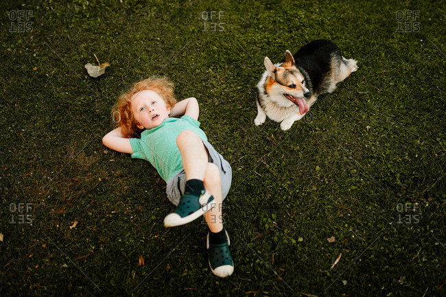Child and dog laying in fresh cut grass