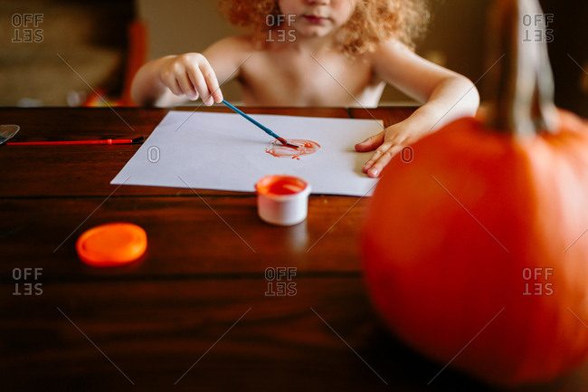 Child painting pumpkin on paper