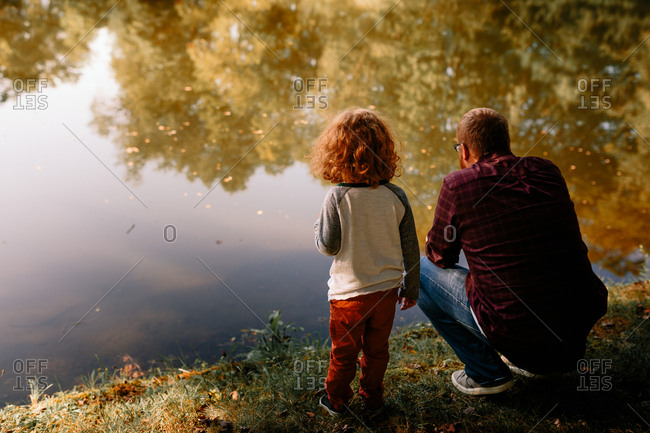 Father and son looking for fish in pond