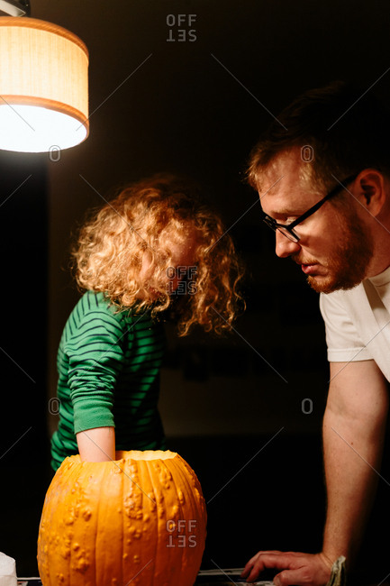 child cleaning out pumpkin for Jack-O-Lantern