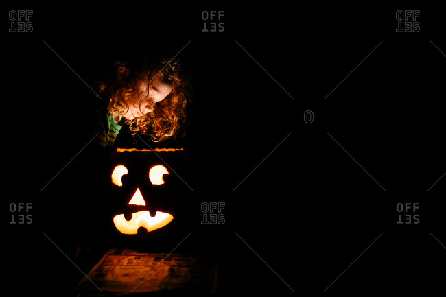 child looking into jack-o-lantern
