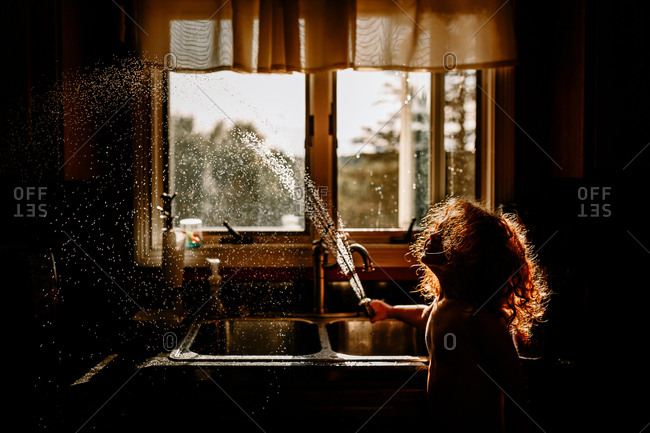 boy playing with spray hose in sink